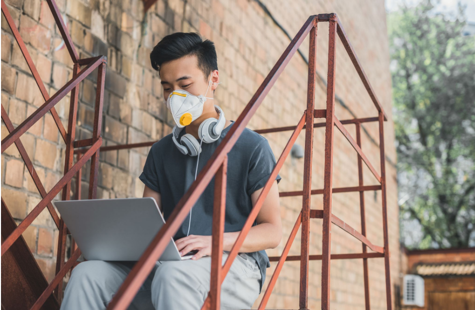 A man working on his laptop while wearing a mask.