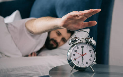 Man waking up early at 6am reaching to shut off his alarm clock